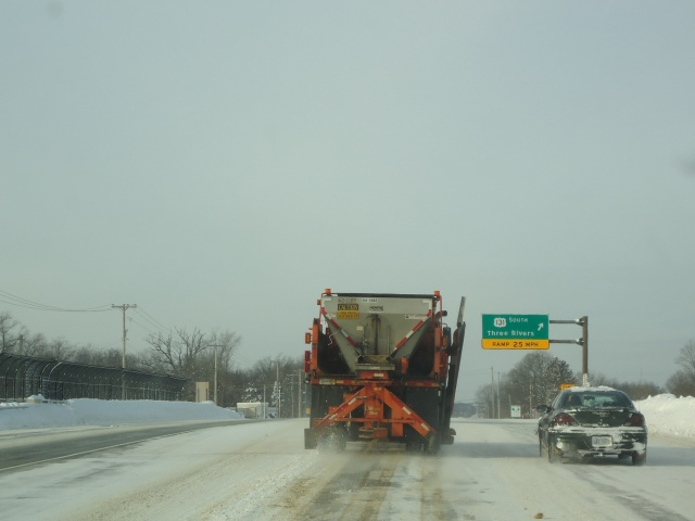 MDOT Spreader Unit applying material for traction after liquid.